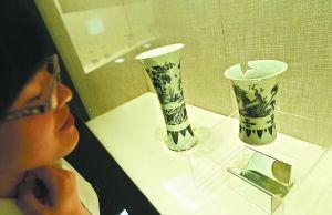 """这是赝品瓷器""""崇祯青花笔筒""""(右)和馆藏真品""""康熙青花花鸟觚""""(左)同台展出。记者 方非摄"""